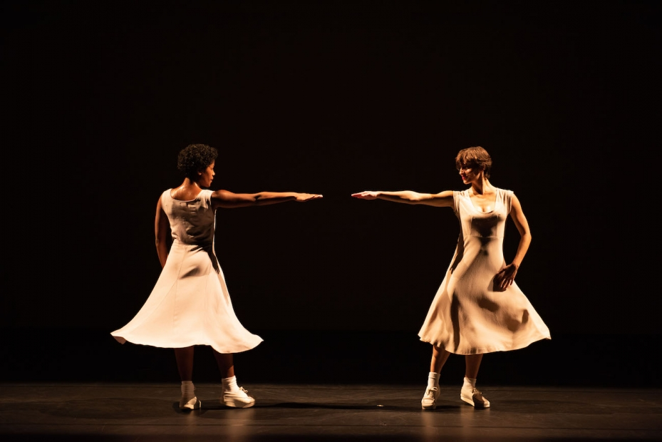 Two female dancers in pale dresses stand on a dark stage with one arm extended toward the other.