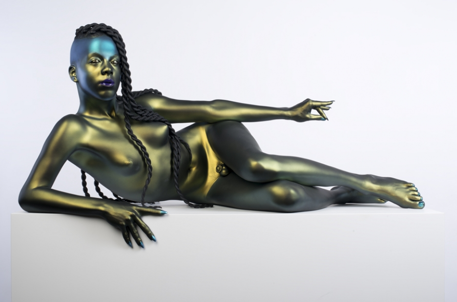 A life-size, hyper realistic bronze sculpture of a nude with long, thick hair in twists, lying on their side, propped up on one elbow with the other hand extended. The finish is a metallic green, except for blue fingernails and purple lipstick.