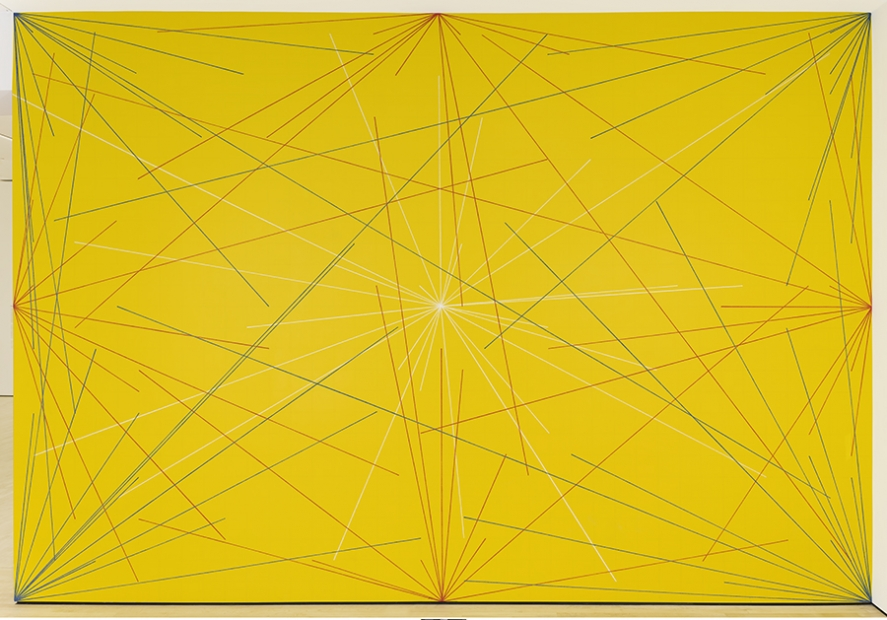 A yellow wall with white, blue, and red lines radiating from the center, corners, and sides.