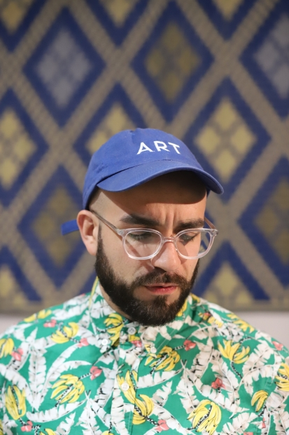 Anthony Febo wearing a cap that says ART and sitting in front of a diamond-patterned wall.