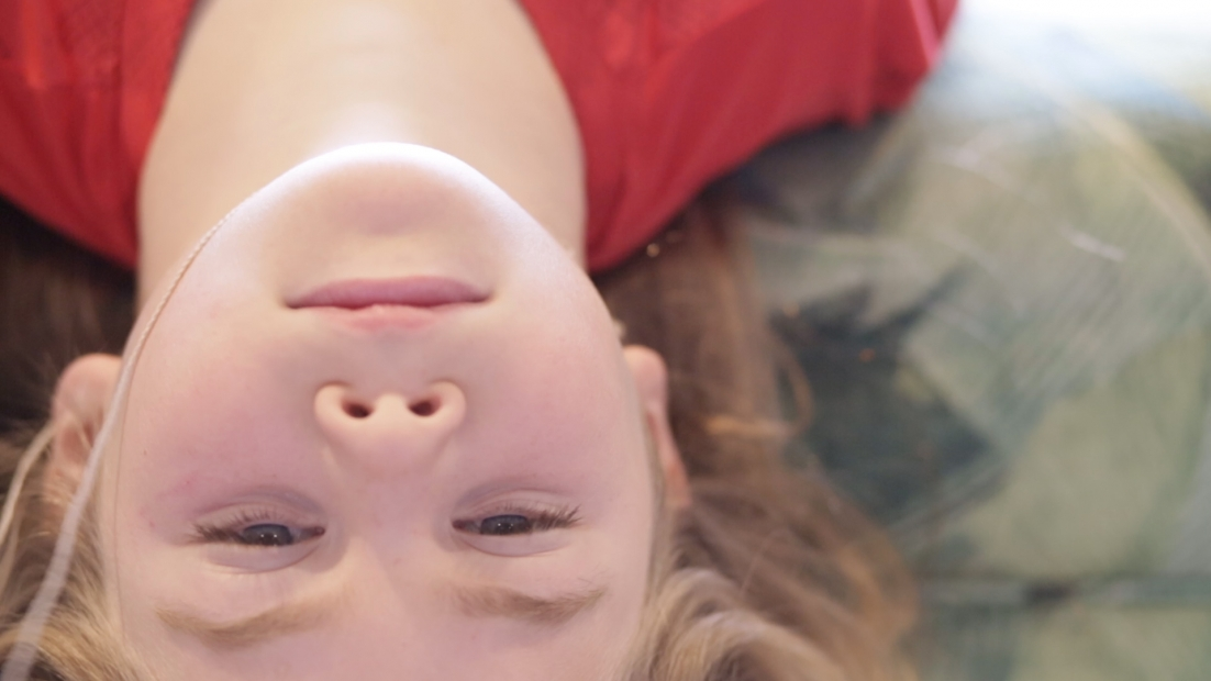 A downward perspective of a young person with the head oriented upside down looking at the camera.