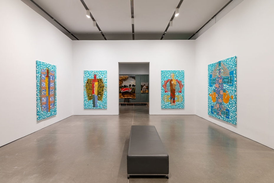 A gallery with four of Marlon Forrester's paintings hanging and the next exhibition in view through the doorway. The paintings all have a multi-colored figure against a teal and white pattern.