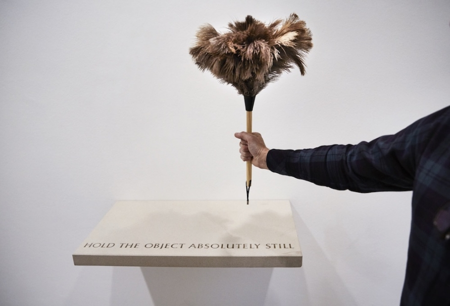 "An arm holding a feather duster over a shelf that says ""Hold the object absolutely still."""