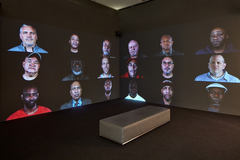 Two adjacent wall-sized screens in a darkened room show a grid of video portraits of men.