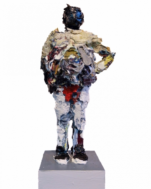 A standing figure that appears to be sculpted from thickly applied oil paint of different colors stands with one hand on his hip, on a small square base.