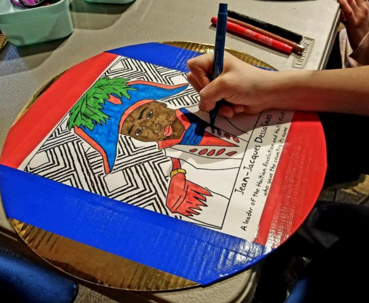 A hand holding a marker coloring in a portrait of Jean-Jacques Dessalines, an African-American figure wearing an 18th-century French-style army uniform.
