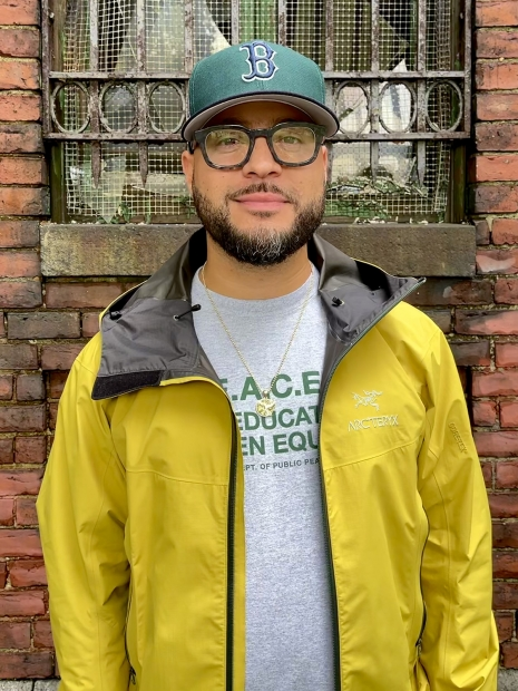 Image of man with Snapback and yellow jacket standing against a brick wall