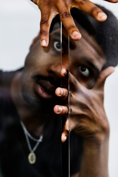 A portrait of an African-American man with his finger tips between a glass crevice.