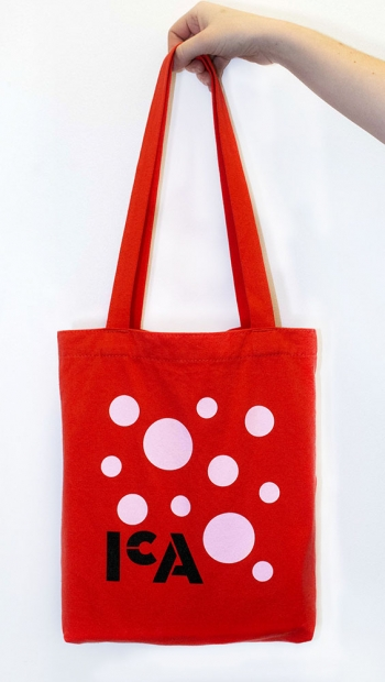 A red tote bag with pink polka dots and the ICA logo in black.