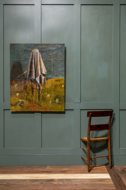 Painting of a figure with a sheet over their head standing in a field of grass hangs on a painted robin's blue paneled wall with a wooden chair installed going through the wall