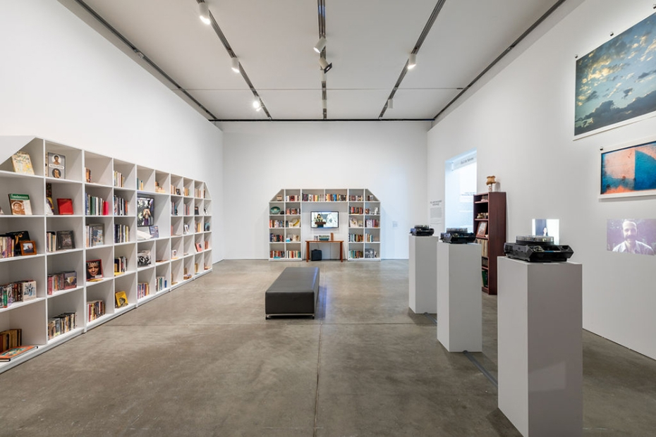 Gallery with large bookshelves filled with books and assorted objects, as well as projected and hanging images along the right wall and a bench in the middle of the room.
