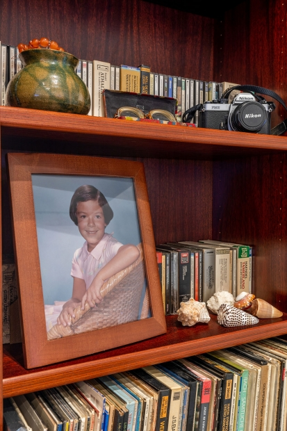 Close up view of a shelf with a framed posed photo of a young girl leaned against CDs and next to 5 seashells. On the shelf above, an old fashioned camera, glasses resting in a case, and a green jar sit in front of more CDs.