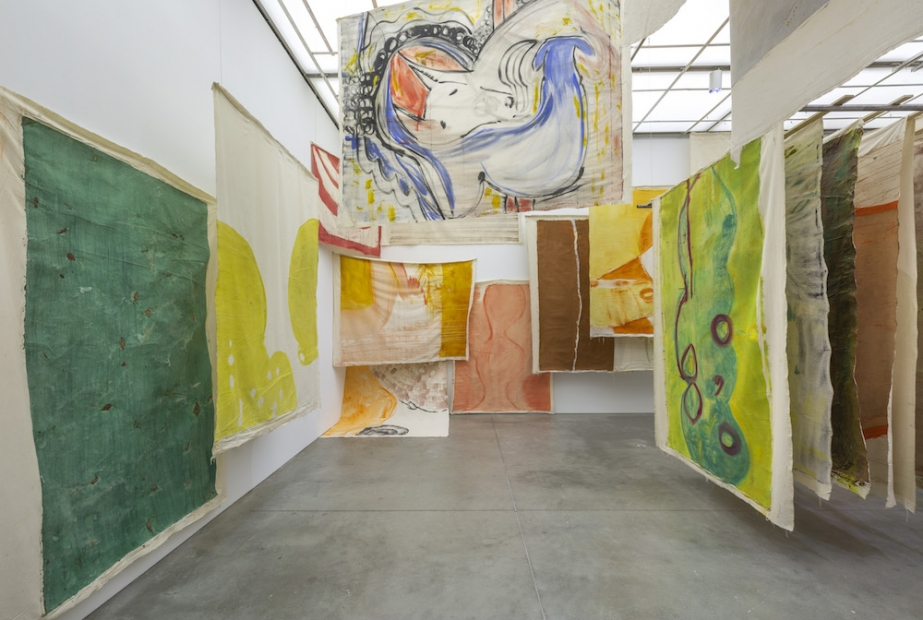 A photograph shows a room full of colorful unframed canvases hung from the ceiling at different angles.