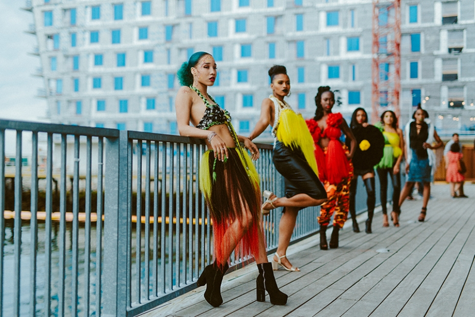 A group of models in colorful clothing outside by the Water at the ICA
