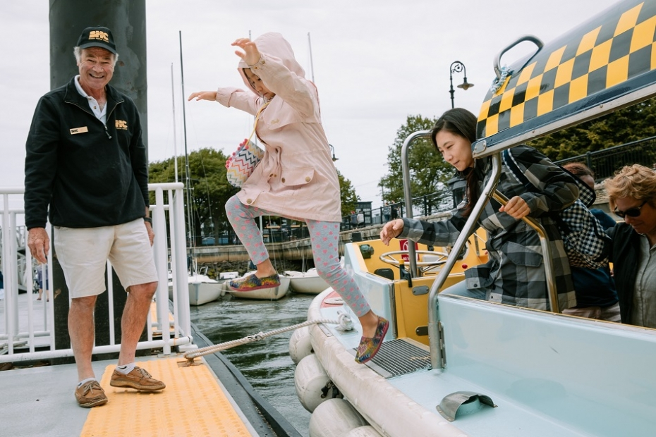 A kid jumping onto the dock from a water taxi while their parent also exits the water taxi and an attendant looks on