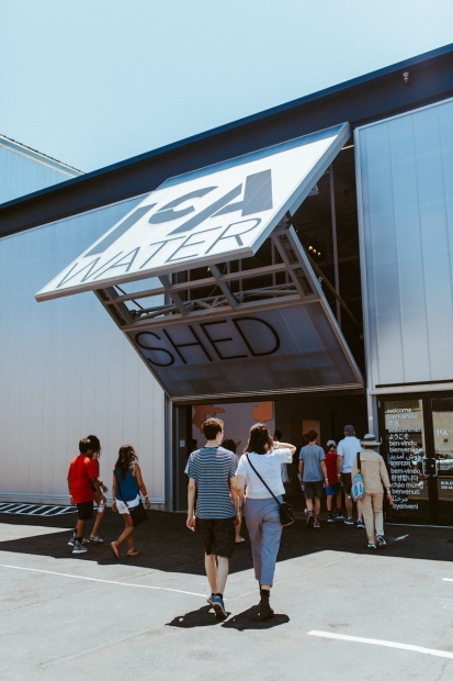 A group of people walk toward and through the open garage-style doors of the ICA Watershed.