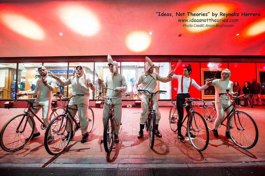 A group of performers in costumes on bicycles on a city street.