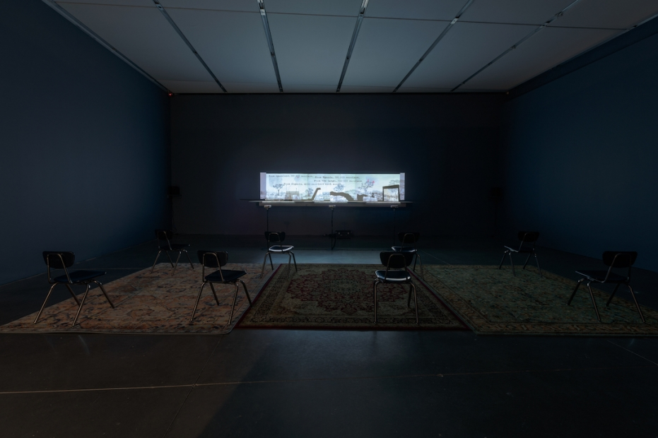 A dark space with a narrow-framed moving images projection illuminating the gallery filled with school chairs and three rugs.