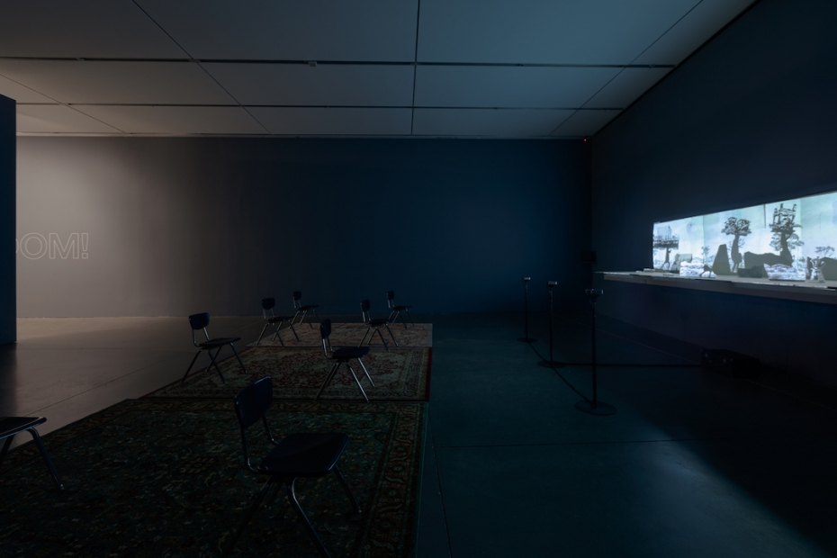 A side angle of a dark space with a moving image projection illuminating the gallery filled with school chairs and three rugs.