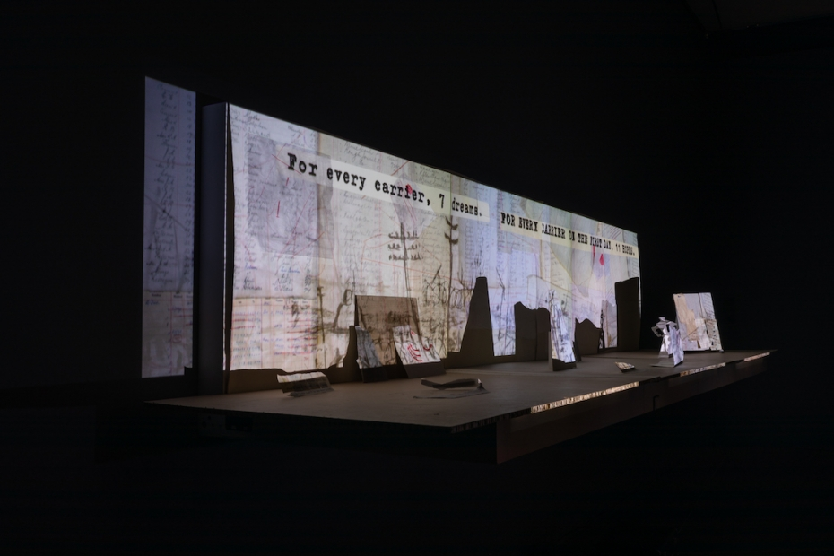 """A close up of miniature paper set pieces, and a projection featuring a collage of letters and documents, drawings, and the words in typewriter """"For every carrier, 7 dreams."""""""