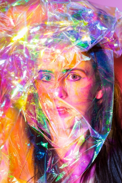 A light skinned redheaded woman with an iridescent plastic sheet over her face in dramatic lighting.