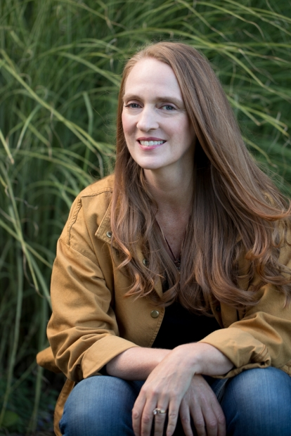 Woman with long, straight brown hair sitting amongst tall grasses