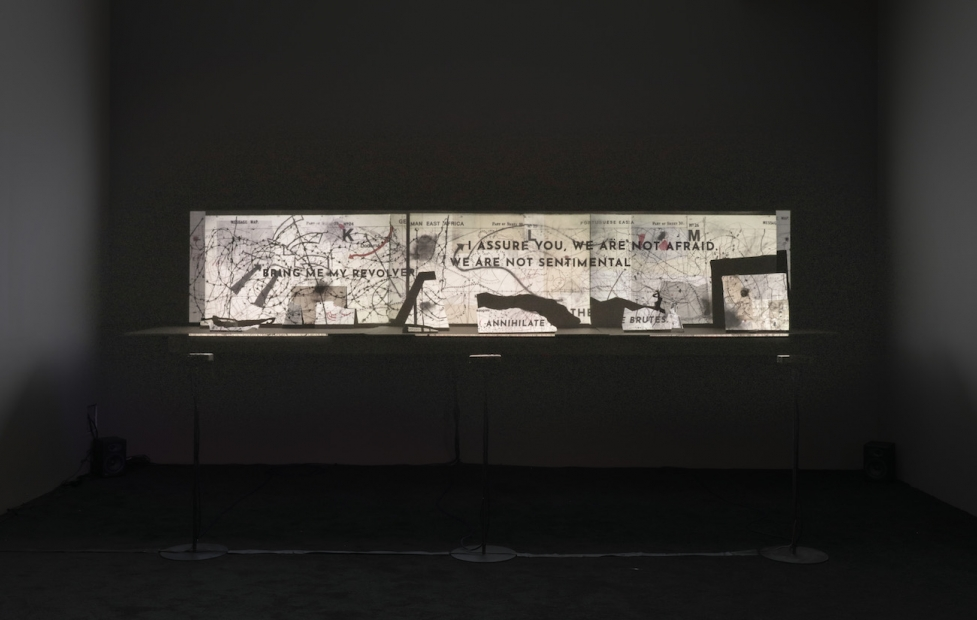 """An installation shows a projection of a map with text that reads """"bring enemy revolverr,"""" """"I assure you, we are not afraid. We are not sentimental,"""" """"annihilate,"""" and """"brutes"""" in all caps and in various parts of the map."""