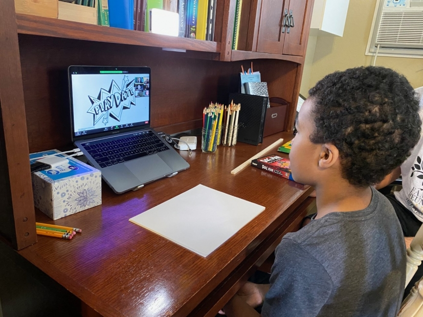 Young Black boy sat at a desk facing a piece of paper and laptop in front of him.