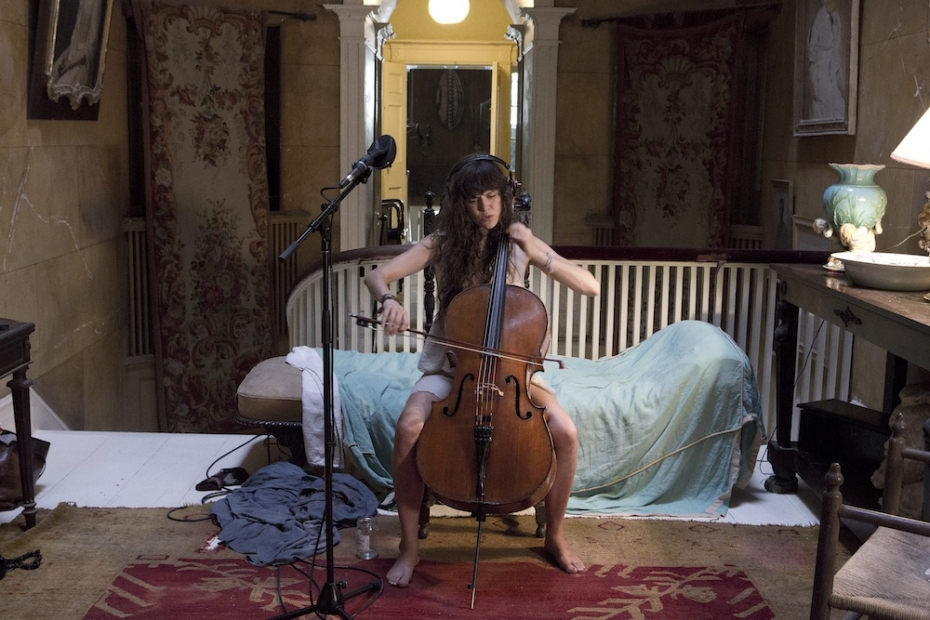 A still from The Visitors with a woman playinge cello.
