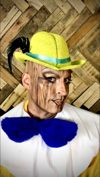 Kurt Fowl wearing a yellow hat, drag makeup, and a blue bow tie.