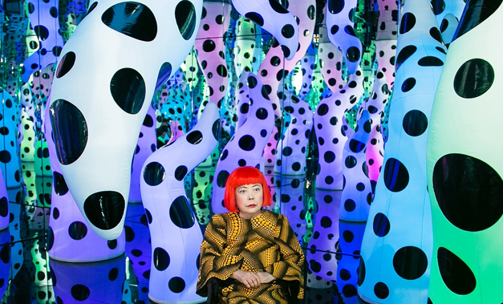 Yayoi Kusama, with bright red hair and a yellow patterned shirt, sits in her Infinity Mirror Room, LOVE IS CALLING.