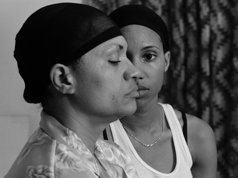 A black-and-white photograph shows the artist, a Black woman, looking directly at the viewer as she stands behind her mother, who is shown in profile and whose head obscures half of the artist's face. Both are wearing hair caps and a curtain is seen in the background.