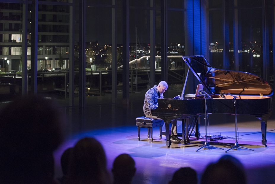 Jason Moran playing the piano in the ICA theater, overlooking the harbor.