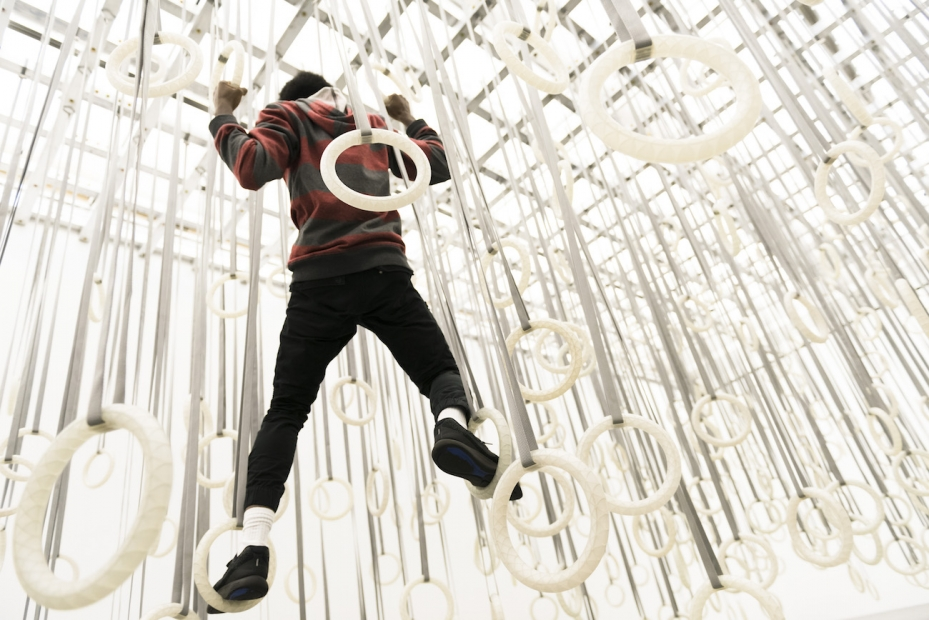 A young man climbs among hundreds of gymnastic rings suspended from the ceiling.