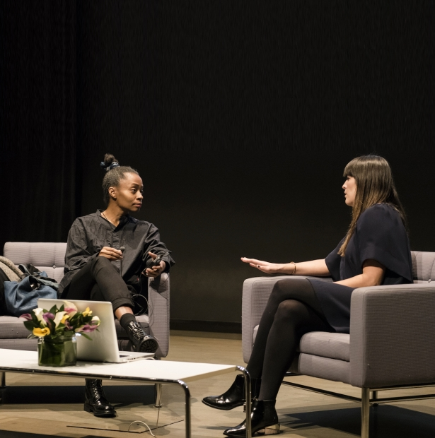 The artist Kara Walker and curator Eva Respini sit and talk onstage in gray chairs against a black background