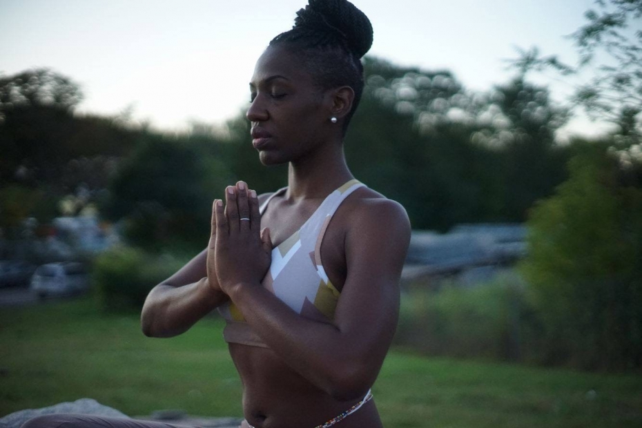 An African-American woman in yoga clothing meditating in a park.