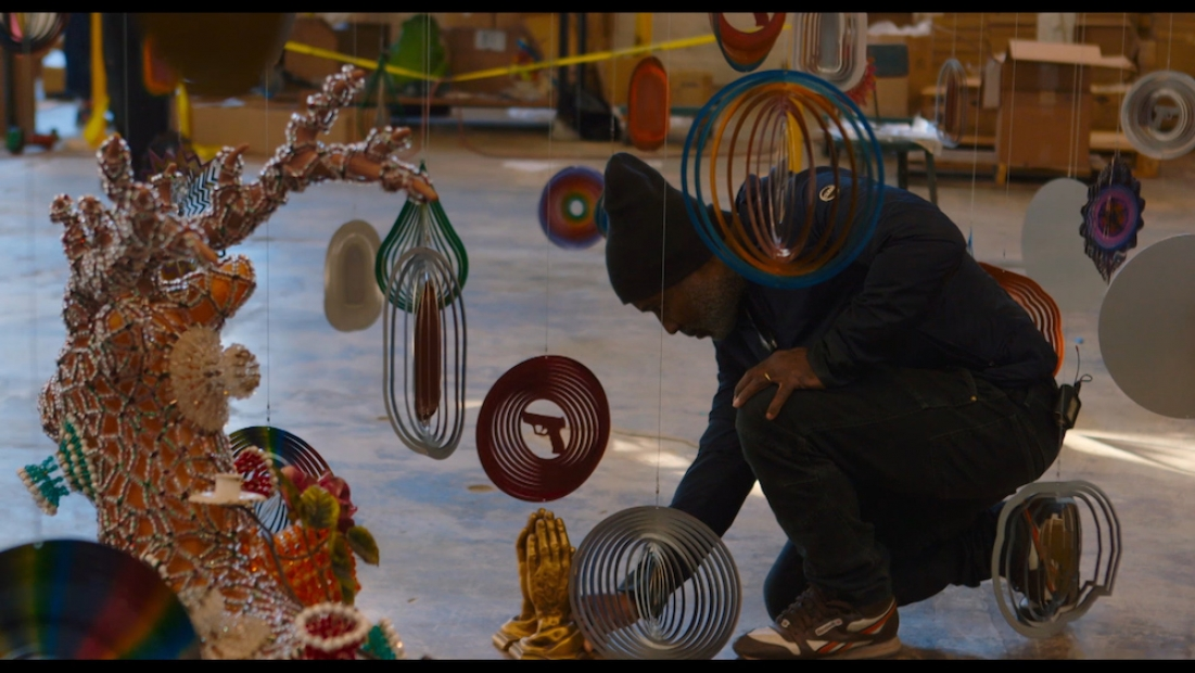 Film still shows artist Nick Cave, in a dark knit hat and clothing, crouching down among multiple hanging decorative reflectors.