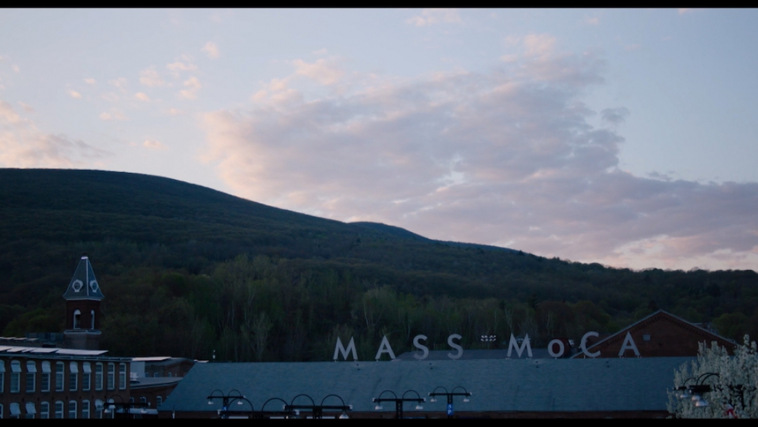 Film still shows the buildings and signage of MASS MoCA against mountains and sky at dusk or dawn.
