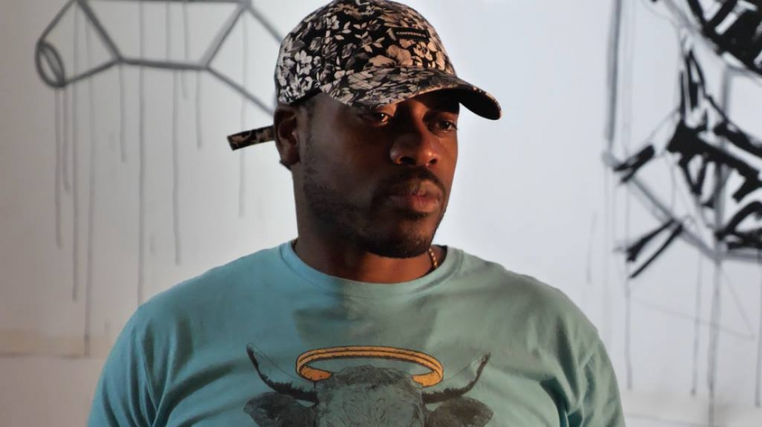 Headshot of Marlon Forrester; a man with dark skin and a baseball hat and graphic tshirt stands in front of art