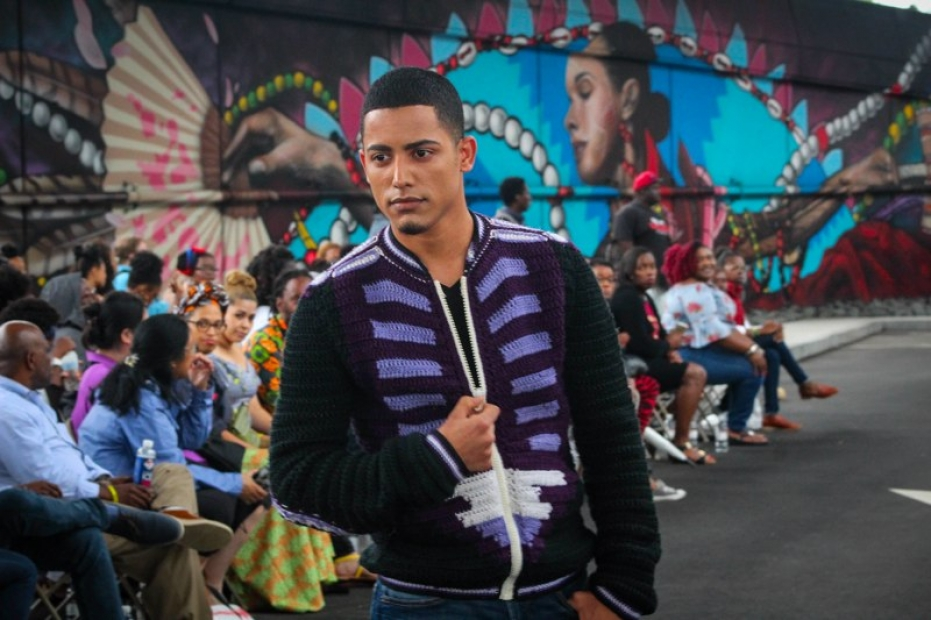 A model in a military-inspired jacket posing in an outside runway show.