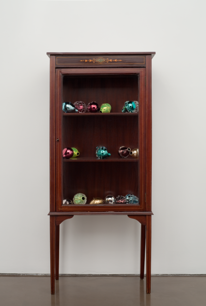 A sculpture comprising an Edwardian wooden cabinet filled with colorful Murano glass grenades that resemble decorative fruit.