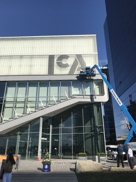 People on a large crane install a new ICA logo on the museum building