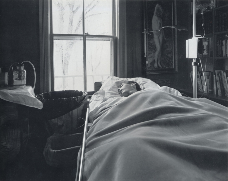 A black-and-white photograph of a man asleep under thick blankets in a home hospital bed, surrounded by an IV and other hospital equipment.