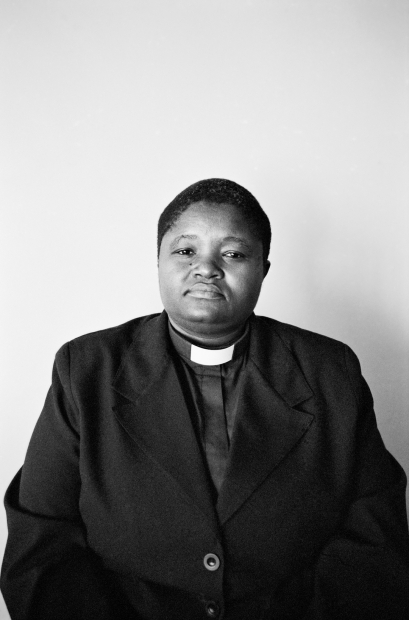 A black-and-white photograph of a person from the waist up wearing a blazer and clergy shirt against a blank wall