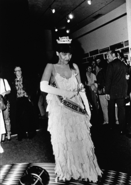A black-and-white photograph of a Black woman in a beauty pageant gown, crown, gloves, bouquet, and sash walking across a crowded gallery while looking down at the floor.