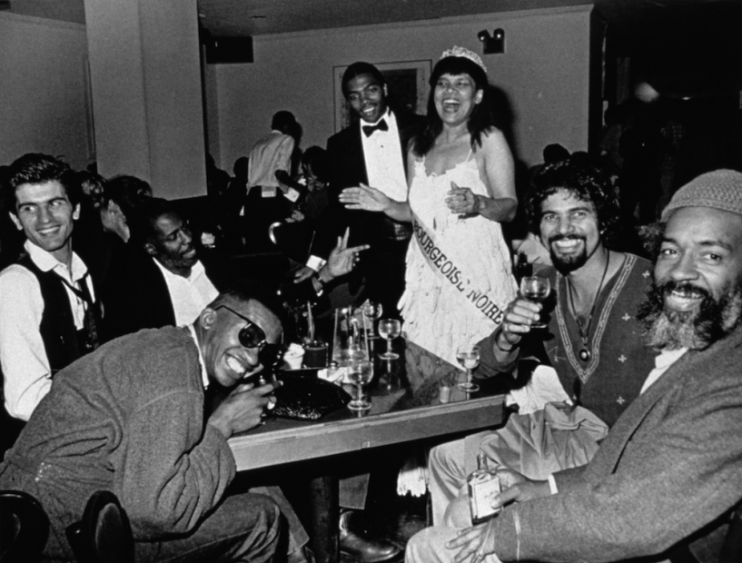A black-and-white photograph of a Black woman in a beauty pageant gown, crown, and sash standing and laughing widely with her arms extended. In front of her are several men seated at a table full of drinks, smiling.