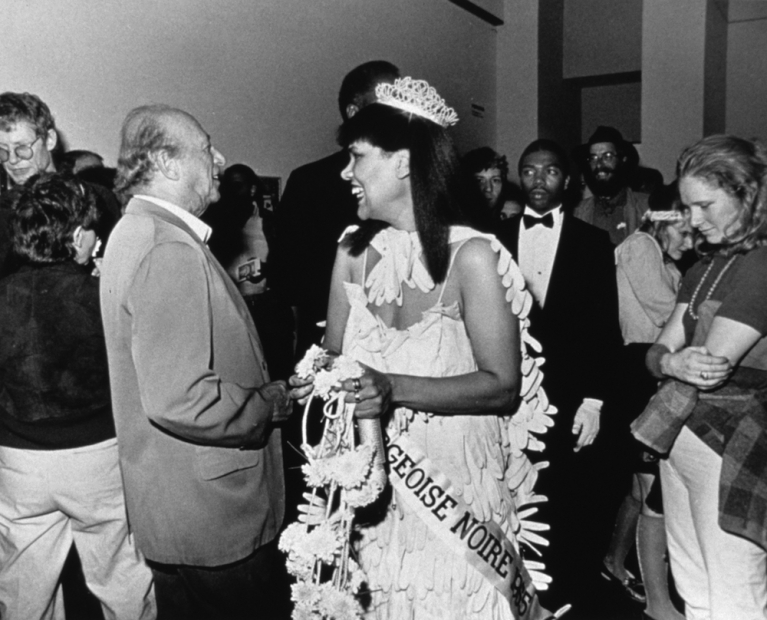 A black-and-white photograph of a Black woman in a beauty pageant gown, crown, gloves, bouquet, and sash in a crowded gallery, smiling at a someone unseen in the image.