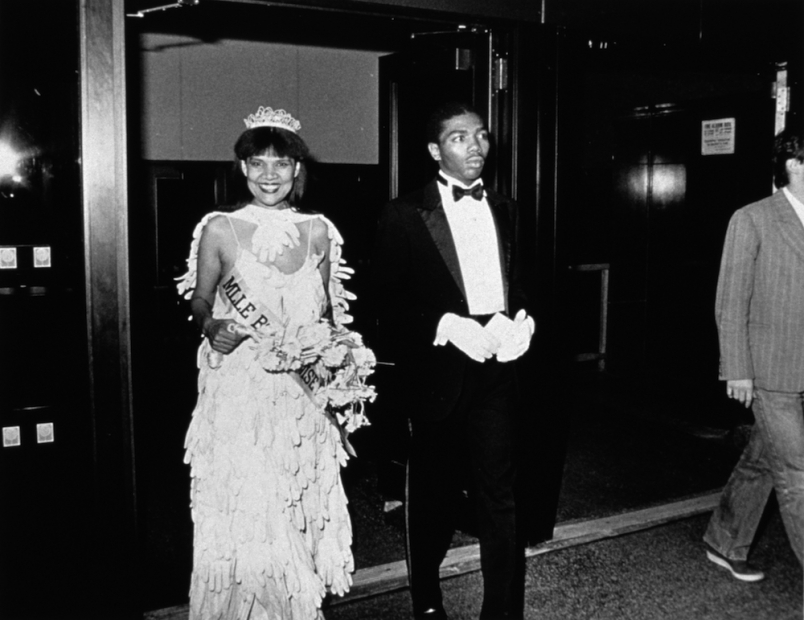 A black-and-white photograph of a smiling Black woman in a beauty pageant gown, crown, gloves, bouquet, and sash is escorted into a room by a young Black man in a tuxedo.
