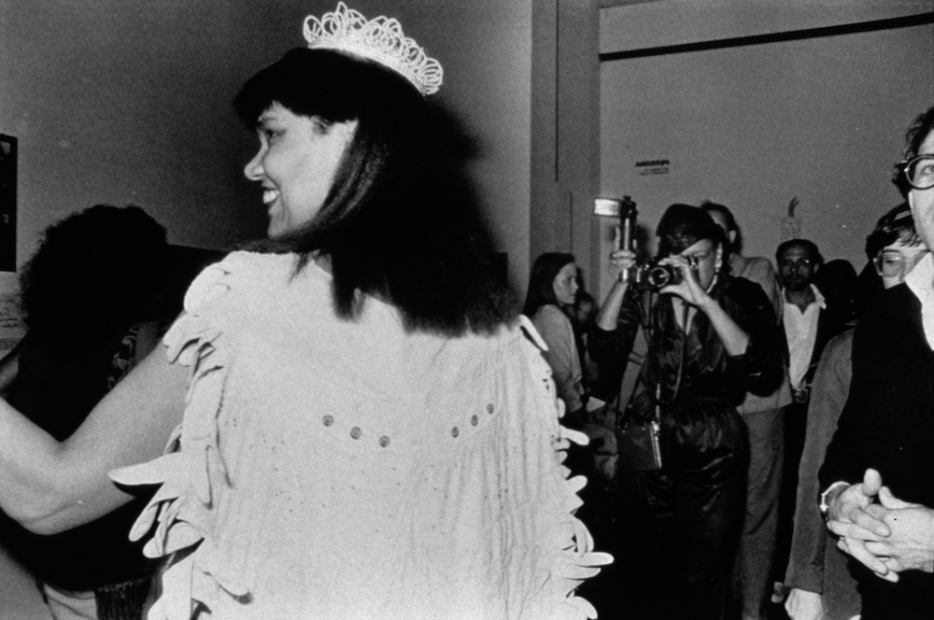 A black-and-white photograph of a Black woman in a beauty pageant gown, crown, gloves, bouquet, and sash is shown in profile as she smiles in profile at someone to her left, while a photographer takes her photo. Her white cape appears made from gloves.