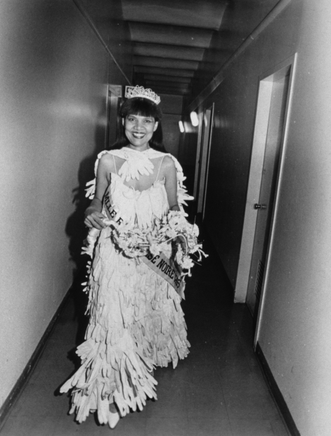 A black-and-white photograph of a Black woman in a beauty pageant gown, crown, gloves, bouquet, and sash  walks down a hallway toward the viewer, smiling widely.